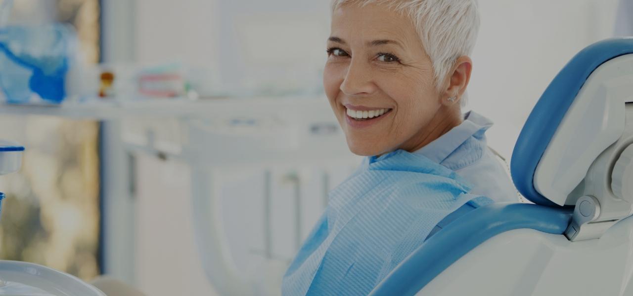 Uśmiechnięta kobieta nafotelu dentystycznym
